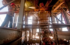 Carl Merworth washes the underside of Robinson Drilling rig #4 on Wednesday, Feb. 17, 2016, in Midland County. The drum-shaped item is the blowout preventer, a large valve designed to seal the drill hole to prevent the uncontrolled release of oil or natural gas. James Durbin/Reporter-Telegram