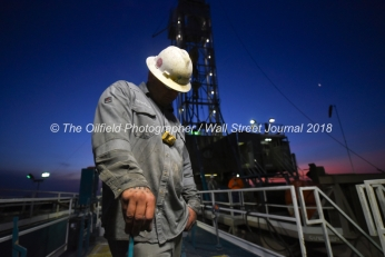 Geoffrey Spencer stands atop a fluid tank while checking the viscosity of mud used in the drilling process, April 11, 2018, on Trinidad Rig 433 operated by Fasken Oil and Ranch north of Midland, Texas. CREDIT: James Durbin / TheOilfieldPhotographer.com MIDLANDOIL