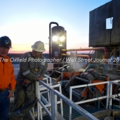 From left, KC Caulder with Octane Energy and Geoffrey Spencer with Trinidad Drilling talk while standing on top of fluid tanks attached to Trinidad Rig 433 operated by Fasken Oil and Ranch, April 11, 2018, north of Midland, Texas. CREDIT: James Durbin / TheOilfieldPhotographer.com MIDLANDOIL