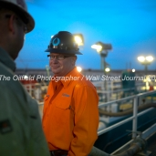 KC Caulder with Octane Energy talks to Geoffrey Spencer with Trinidad Drilling while standing on top of fluid tanks attached to Trinidad Rig 433 operated by Fasken Oil and Ranch, April 11, 2018, north of Midland, Texas. CREDIT: James Durbin / TheOilfieldPhotographer.com MIDLANDOIL