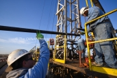Juan Carrasco with Fasken Oil and Ranch, left, assists a pulling unit crew to install a pumpjack on a well site, April 11, 2018, north of Midland, Texas. CREDIT: James Durbin / TheOilfieldPhotographer.com MIDLANDOIL