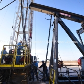 A pulling unit crew installs a pumpjack on a well site, April 11, 2018, north of Midland, Texas. CREDIT: James Durbin / TheOilfieldPhotographer.com MIDLANDOIL