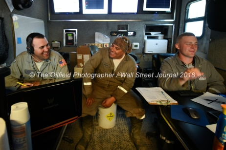 Cudd Energy employees from left, Taylor Moore, Martin Del Campo, and Xyler Reynolds oversee a fracking stage from inside a mobile trailer at a Fasken Oil and Ranch well site May 22, 2018, in Midland, Texas. CREDIT: TheOilfieldPhotographer.com