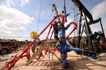 A wireline hand prepares to connect a perforating gun to the top of a wellhead at a Cudd Energy fracking operation on a Fasken Oil and Ranch well May 22, 2018, in Midland, Texas. CREDIT: TheOilfieldPhotographer.com