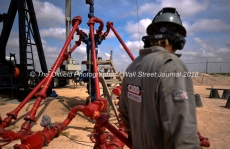 David Cantu, line boss, walks near a wellhead at a Cudd Energy fracking operation on a Fasken Oil and Ranch well May 22, 2018, in Midland, Texas. CREDIT: TheOilfieldPhotographer.com