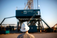 """Trinidad Drilling rig 224 at sunrise is visible behind a Parsley Energy employee's hardhat reading """"Think Safety"""" on Tuesday, July 18, 2017 in Reagan County, Texas.. James Durbin for the Wall Street Journal"""