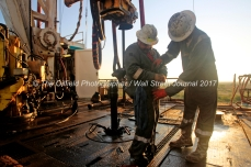 Floorhands Juan Franco, left, and Josh Latham, right, work to attach sections of pipe onboard Trinidad Drilling rig 224 Tuesday, July 18, 2017 in Reagan County, Texas.. James Durbin for the Wall Street Journal