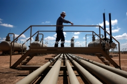 Lease operator Casey Wallace crosses over pipes at a Parsley Energy oil well facility Tuesday, July 18, 2017, in Midland County. James Durbin for the Wall Street Journal
