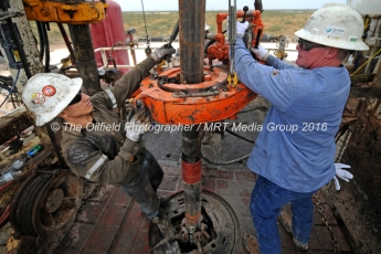 Noe Olvera, left, and Kevin Giddings, right, add a section of casing down a vertical well on the floor of Trinidad Rig 433 on Wednesday, Nov. 2, 2016, in Midland County. James Durbin/Reporter-Telegram